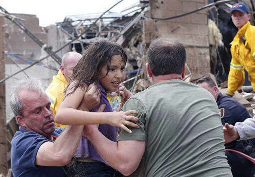 A child being rescued from one of the two schools completely destroyed by todays tornado. These two, Plaza Tower and Briarwood Elementary, were just two of five schools to suffer damage)